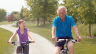 TS Grandfather and granddaughter cycling through the park