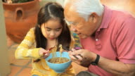 MS Grandfather and Granddaughter (8-9) eating hot noodle soup with chopsticks / Los Angeles, California, USA