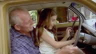 CU, Grandfather and granddaughter (10-11) pretending to drive car, Tamborine Mountain, Brisbane, Queensland, Australia