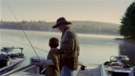 Grandfather and grandson carrying fishing poles to motorboat on dock / grandfather helping grandson step onto boat