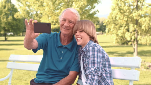 Grandfather and grandson making a selfie on park bench