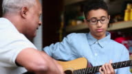 CU PAN Grandfather and Grandson Playing Guitar Together in Garage / Richmond, Virginia, United States