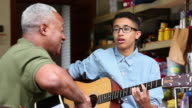 MS Grandfather and Grandson Playing Guitar Together in Garage / Richmond, Virginia, United States
