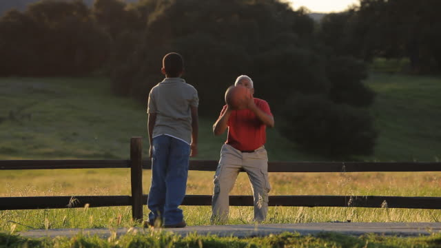 WS Grandfather and grandson (6-7) playing with basketball on field / Los Angeles, California, USA