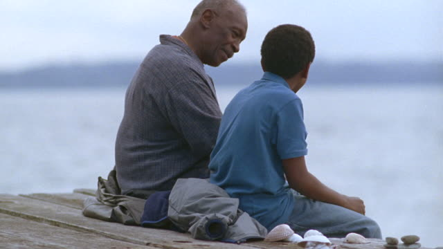 MS Grandfather and grandson talking and sitting on pier near lake / Washington State, USA