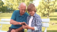 Grandfather and grandson using a phone while sitting in park