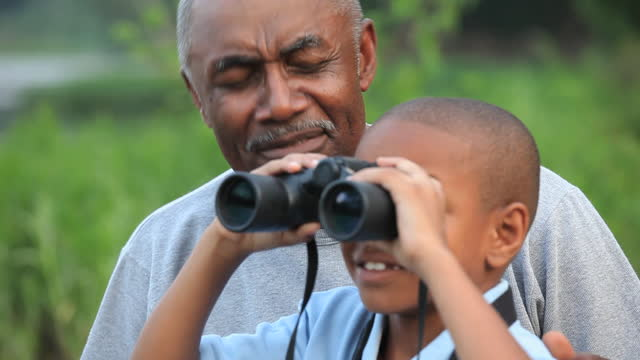 CU Grandfather and grandson (8-9) using binoculars outdoors / Richmond, Virginia, USA