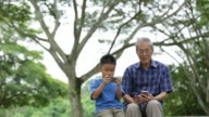 MS Grandfather and grandson using mobiles phone and devices