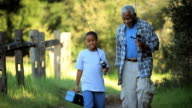 MS Grandfather and grandson (8-9) walking on field with fishing poles on their shoulders / Los Angeles, California, USA