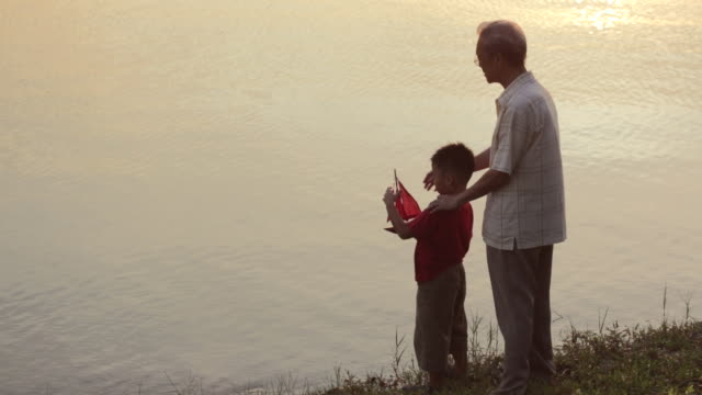 WS Grandfather and Grandson with model boat looking at lake