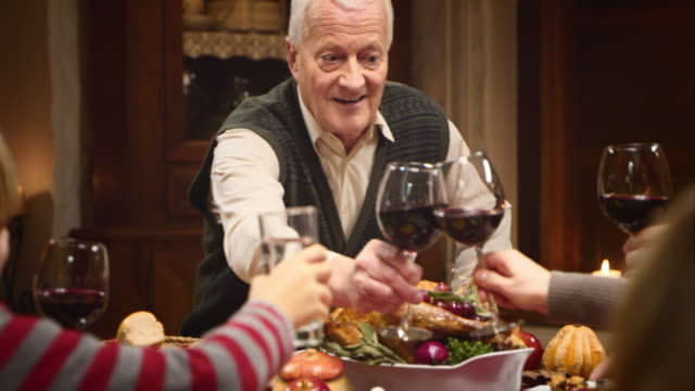 Grandfather clinking glasses with his family at Thanksgiving table