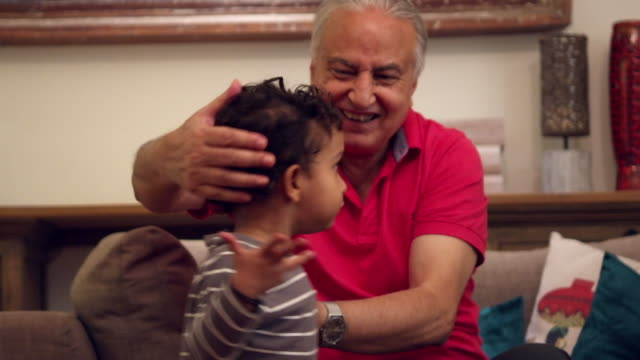 A grand-father comforts one of the twins after they bang each other's head, he comforts them