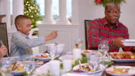 Grandfather coordinates dishes as family passes them around the table for Christmas dinner (dolly-shot)