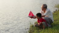 MS Grandfather helping  grandson with model boat at lake