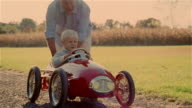 CU, grandfather pushing boy (4-5 years) driving toy car on graver driveway, USA, Pennsylvania, Solebury