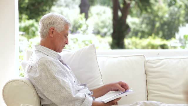 Grandfather Reading On Sofa When Grandchildren Give Him A Cuddle