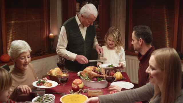 Grandfather serving turkey slices onto granddaughters plate