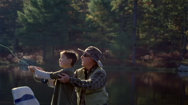 Grandfather showing grandson how to cast fly fishing line