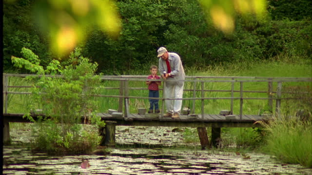 A grandfather teaches his grandson how to fish in a reflective pond.