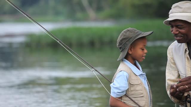 MS PAN Grandfather teaching grandson (8-9) about fly fishing / Richmond, Virginia, USA