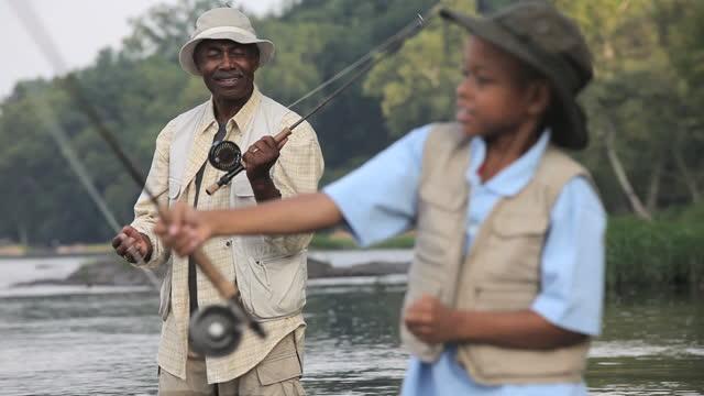 MS TU Grandfather teaching grandson (8-9) how to cast fly fishing / Richmond, Virginia, USA