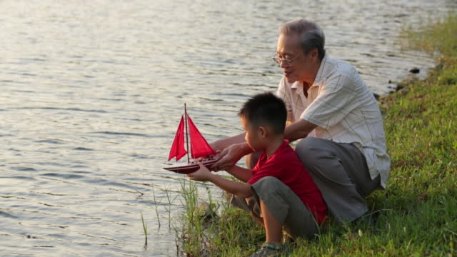 MS Grandfather teaching  grandson with model boat at lake