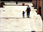 Grandfather walking with little girl