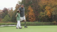 WS PAN Grandfather with two prosthetic legs and grandson (8-9) walking on golf course / Richmond, Virginia, USA