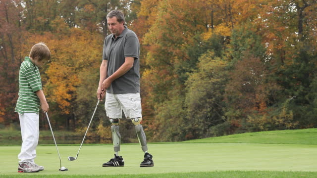WS PAN Grandfather with two prosthetic legs teaching grandson (8-9) how to play golf / Richmond, Virginia, USA