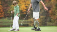 MS PAN Grandfather with two prosthetic legs teaching grandson (8-9) how to play golf / Richmond, Virginia, USA