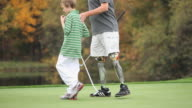 MS PAN TU Grandfather with two prosthetic legs teaching grandson (8-9) how to play golf / Richmond, Virginia, USA