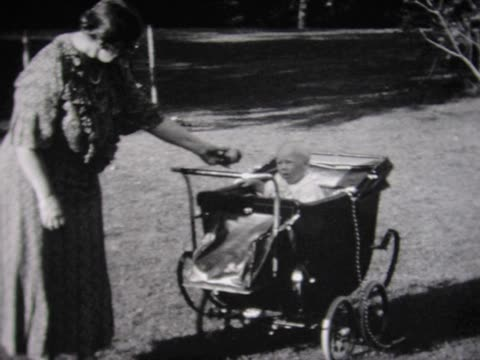1935 grandma pushes baby in old carriage