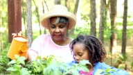 Grandmother and children gardening outdoors in spring.