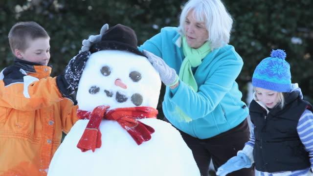 MS TU TD Grandmother and grandchildren (4-9) making snowman / Richmond, Virginia, USA