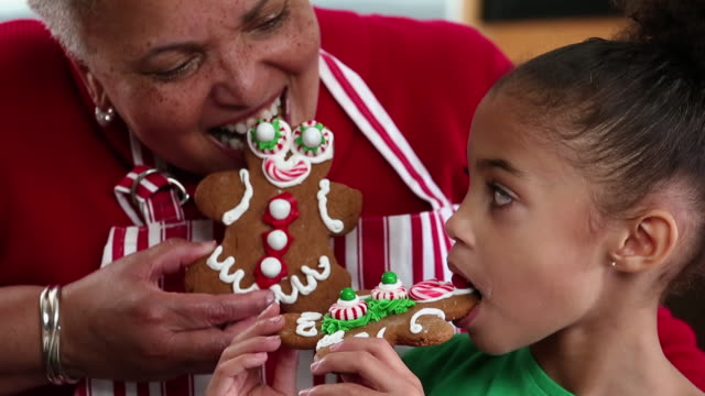 CU Grandmother and Granddaughter Eating Gingerbread Men Cookies in Kitchen / Richmond, Virginia, USA