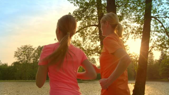 SLO MO-TS Großmutter und Enkelin jogging bei Sonnenuntergang