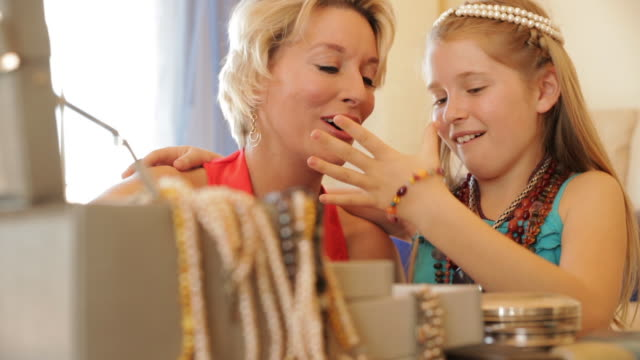 Grandmother and granddaughter playing with jewellery together indoors.