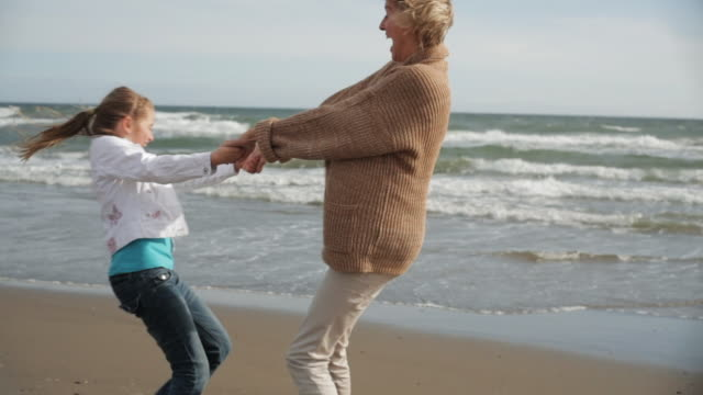 Grandmother and granddaughter twirling together on windy beach.