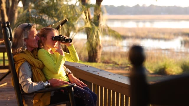Grandmother and her 8 year old granddaughter on vacation using binoculars