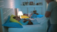 MS Grandmother pulling duvet up and kissing sleeping daughter good night then turning light off, Panama City, Panama