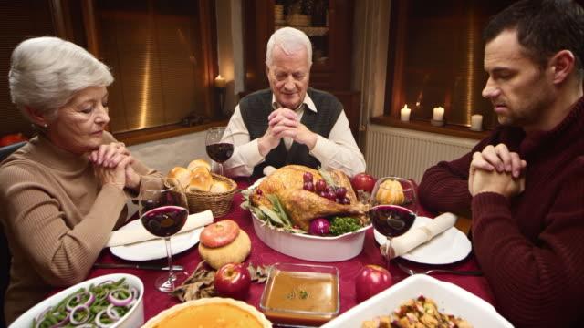 Großmutter Tischgebet am Thanksgiving Tabelle mit Ihrer Familie