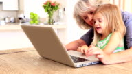 Grandmother using laptop with her granddaughter