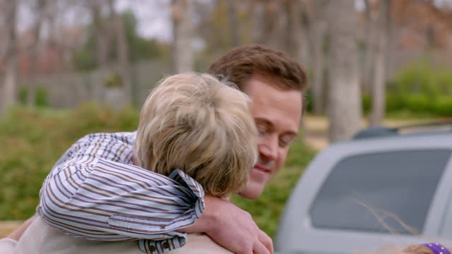 Grandmother welcomes and hugs teenage grandson and son-in-law