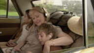 MS, Grandmother with granddaughter (10-11) and grandson (6-7) listening to music on car back seat, Tamborine Mountain, Brisbane, Queensland, Australia