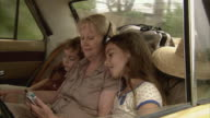 MS, Grandmother with granddaughter (10-11) listening to music on car back seat, boy (6-7) sleeping, Tamborine Mountain, Brisbane, Queensland, Australia