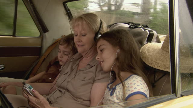 MS, Grandmother with granddaughter (10-11) listening to music on car back seat, boy (6-7) sleeping, Tamborine Mountain, Brisbane, Queensland, Australia