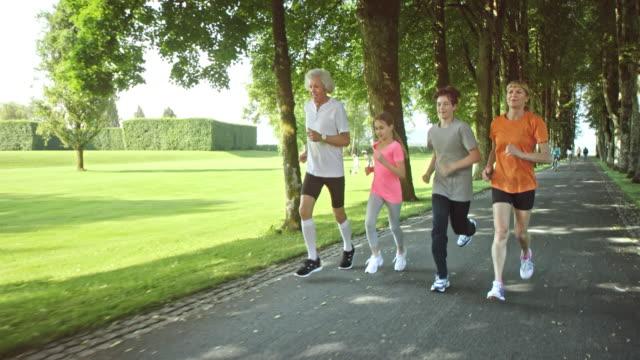 SLO MO TS Grandpa and grandma jogging with grandchildren