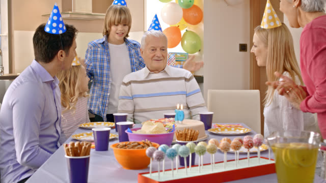 Grandpa getting surprise cake for birthday from his family