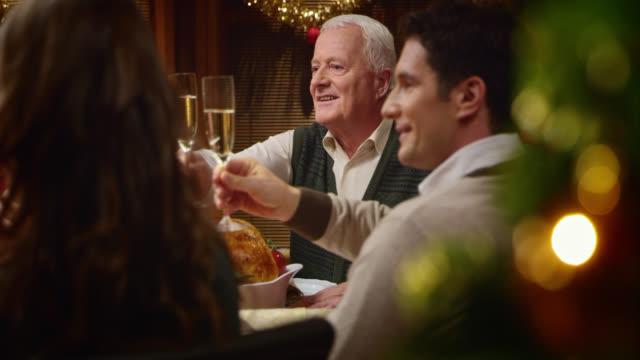 SLO MO  grandpa making a toast at the Christmas table