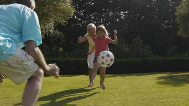 Grandparents and granddaughter playing football in garden.